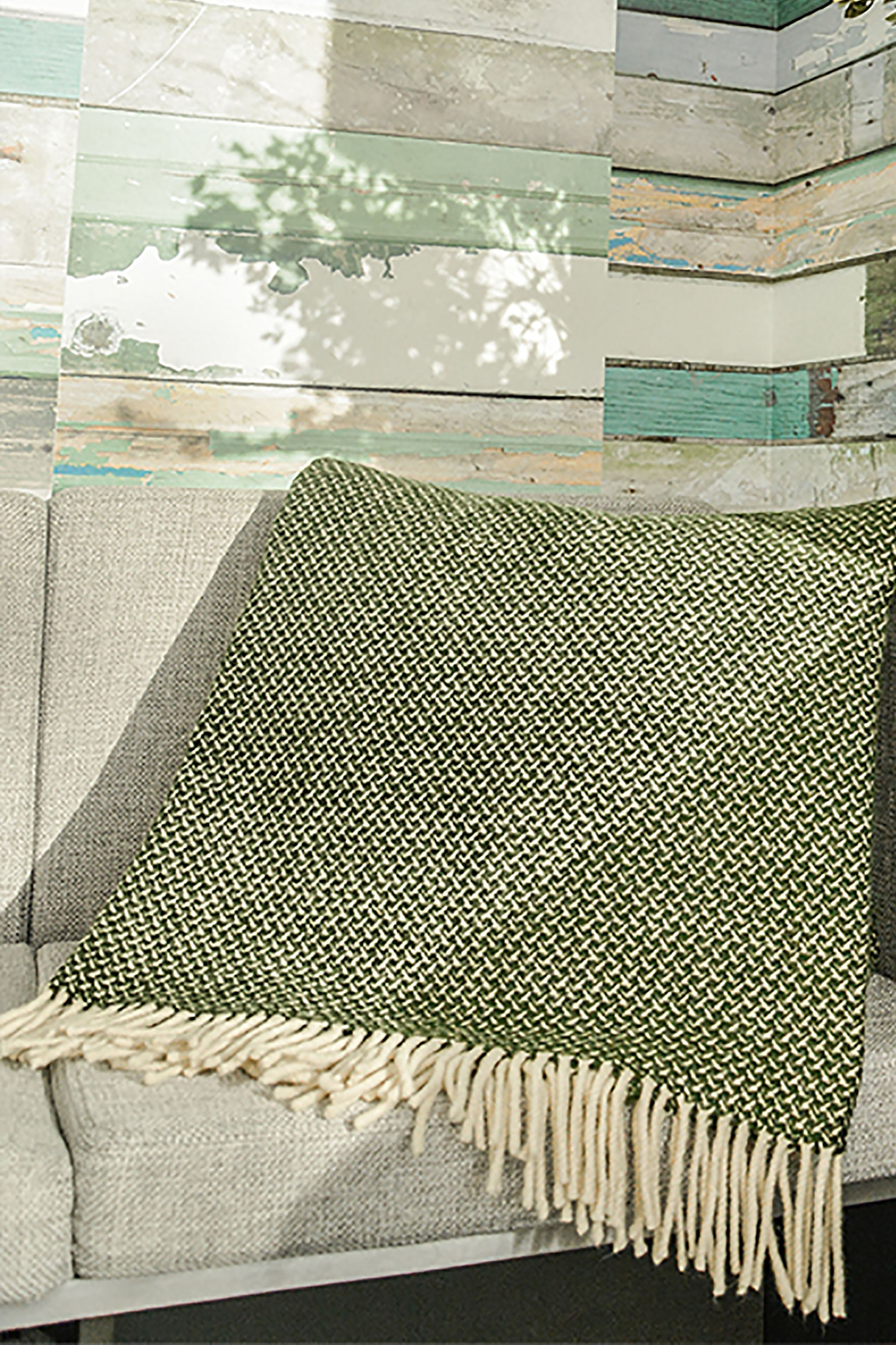 Dry green Merino wool throw with tight wing pattern and fringe folder over sofa