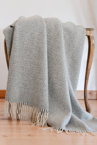 Light gray Merino wool throw with chevron weave and fringe, folded over a side table