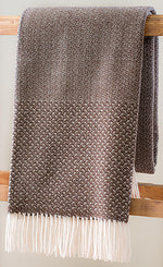 Brown Merino wool throw with cloud weave in middle and tight wings on ends with fringe, folded over ladder