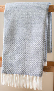 Light gray Merino wool throw with cloud weave in middle and tight wings on ends with fringe, folded over ladder