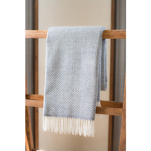 Asterlark merino wool throw blanket in light gray with wing weave pattern on the borders of two sides