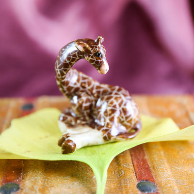 Miniature laying giraffe figurine