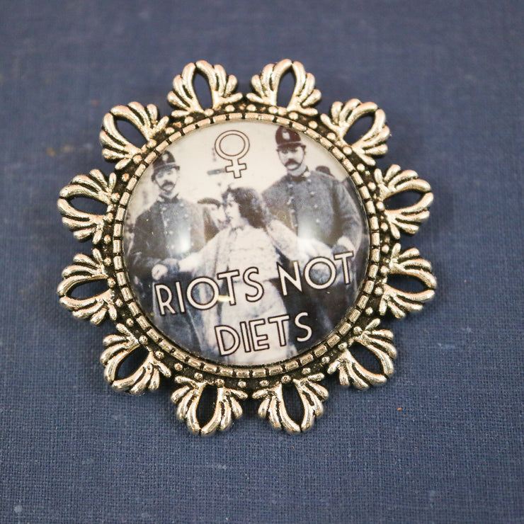 Riots not diets round brooch