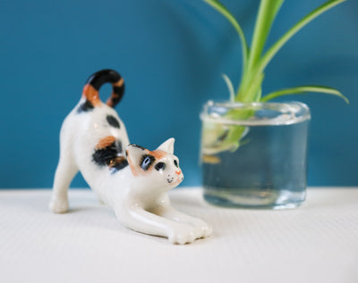 Miniature stretching cat figurine