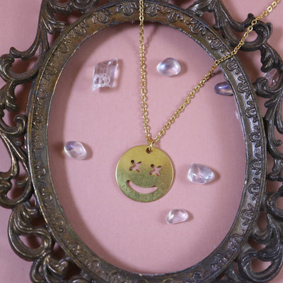 Cross eyed smiley necklace