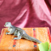 Small lounging otter figurine