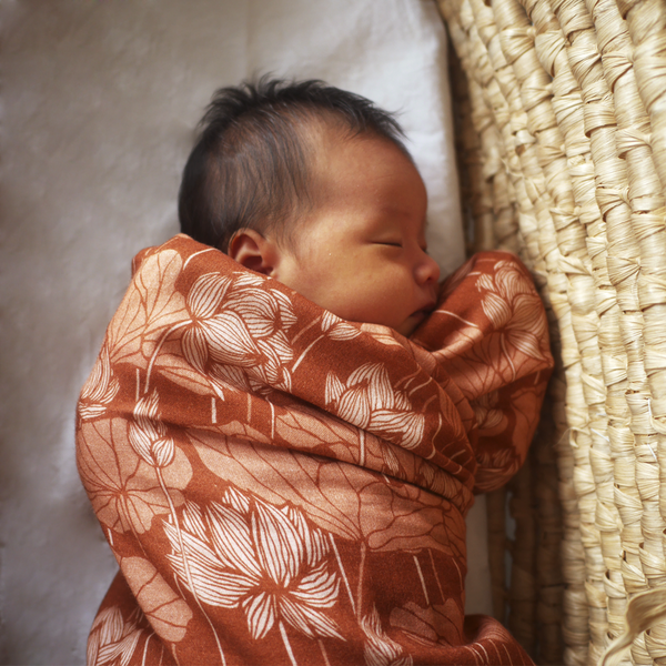 Baby swaddled in Desert Lotus Muslin wrap