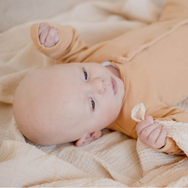 Baby laying on Ivory muslin wrap
