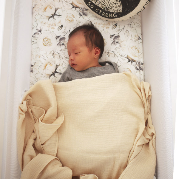 Baby swaddled in Ivory muslin wrap sleeping in bassinet