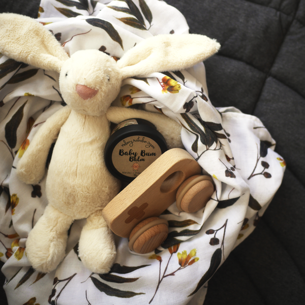 Gumnuts and Gold muslin wrap styled with jellycat bunny, baby bum balm and wooden toy car