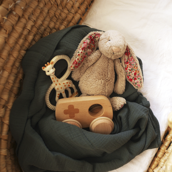 Lush pine muslin wrap styled with jellycat bunny, sophie the giraffe teether and wooden toy car