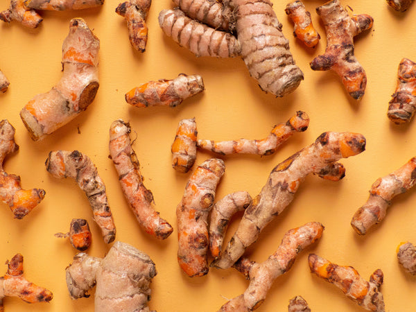 A photo of raw turmeric root used for inflammation and muscle soreness on a yellow background
