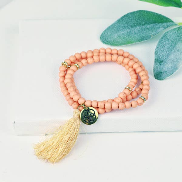 Blush beaded stretch bracelet, tassel
