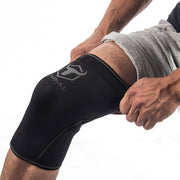 black-gray knee support sleeves how to put on