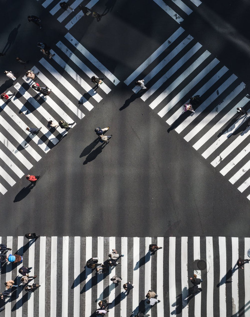 Intersection showing multiple directions of crosswalks with people crossing