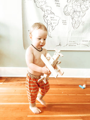 Child playing with a Wooden Toy Airplane