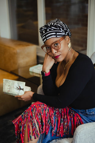 Woman seated with book wearing African print head wrap