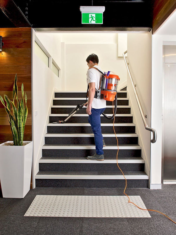 Commercial cleaner walking up staircase while vacuum cleaning Commercial cleaner walking up staircase while vacuum cleaning with the Advantage Ultimate Turbo Combo