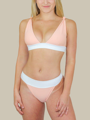 The ELLEJAY Buzios Top features a shoulder knot tie and thick band. This Bikini top is a blush pink with contrasting white colors.