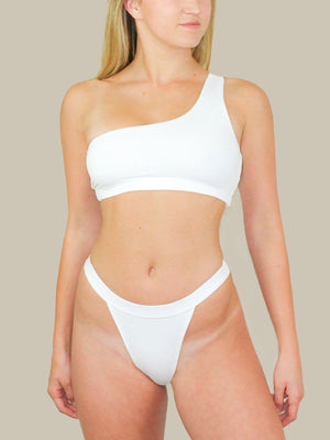 This picture features 437 Swimwear's The Roy Top. This top features white seamless fabric with one-shoulder detail. This top also has an elastic waistband at the hem.