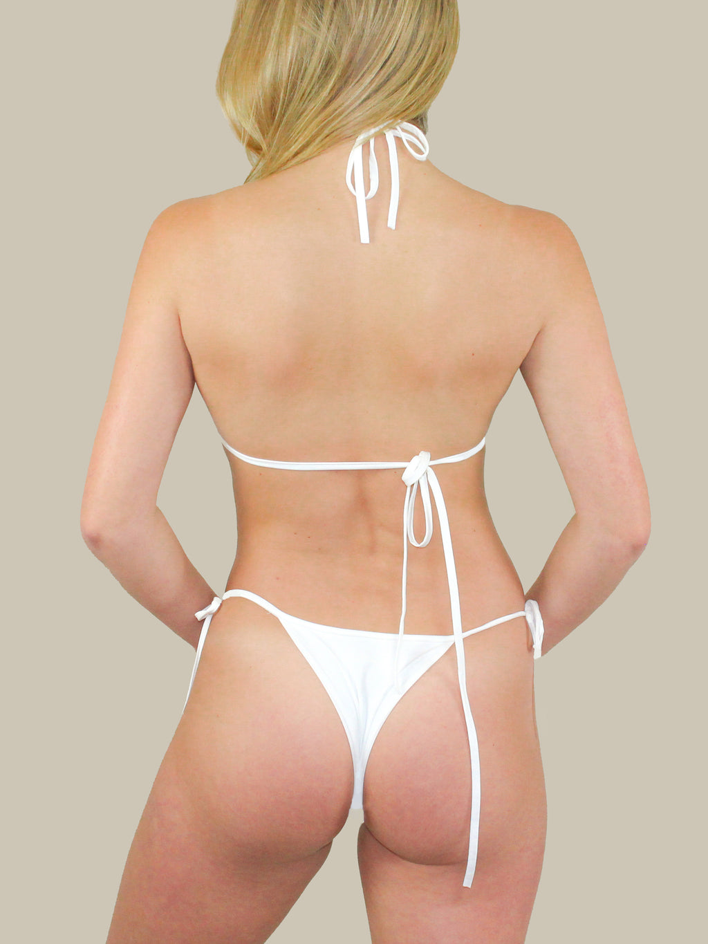 437 Swimwear's The Sander's Bottoms feature a white seamless fabric with side ties. These bottoms have minimal coverage and are perfect for tanning outdoors.