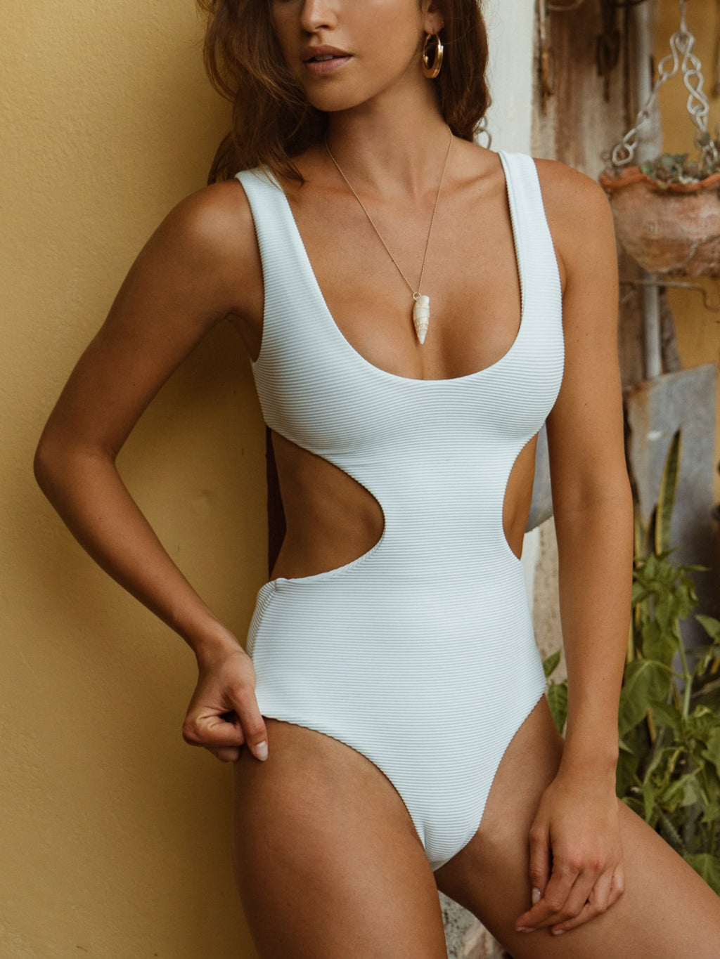 The Citrine Swim Nolita One Piece is a light blue color and is ribbed throughout. This one piece bikini has side cut-outs and an adjustable back tie.
