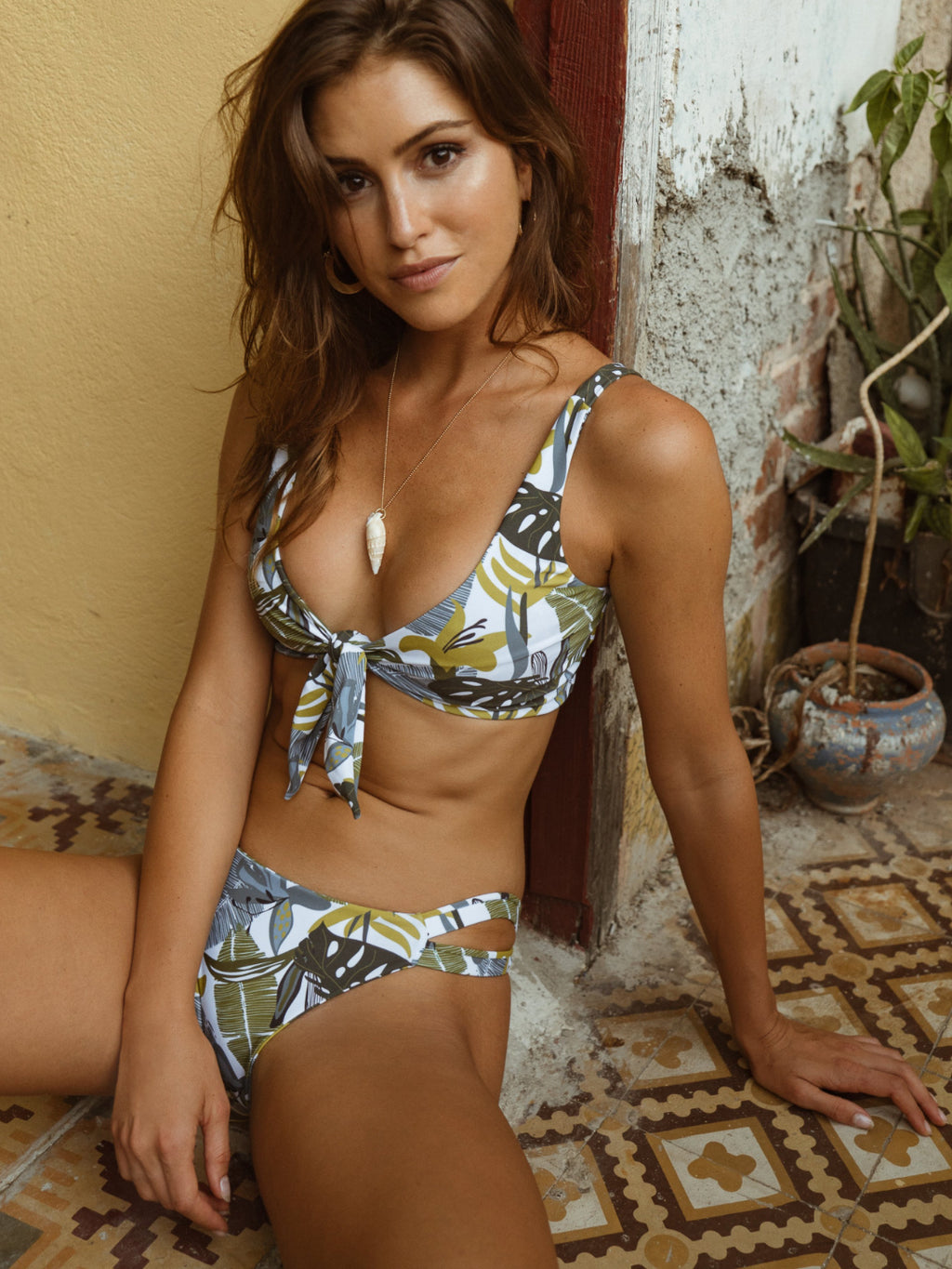 This bikini top features a front tie and is reversible. This bikini top has a palm print that is bright green and blue.