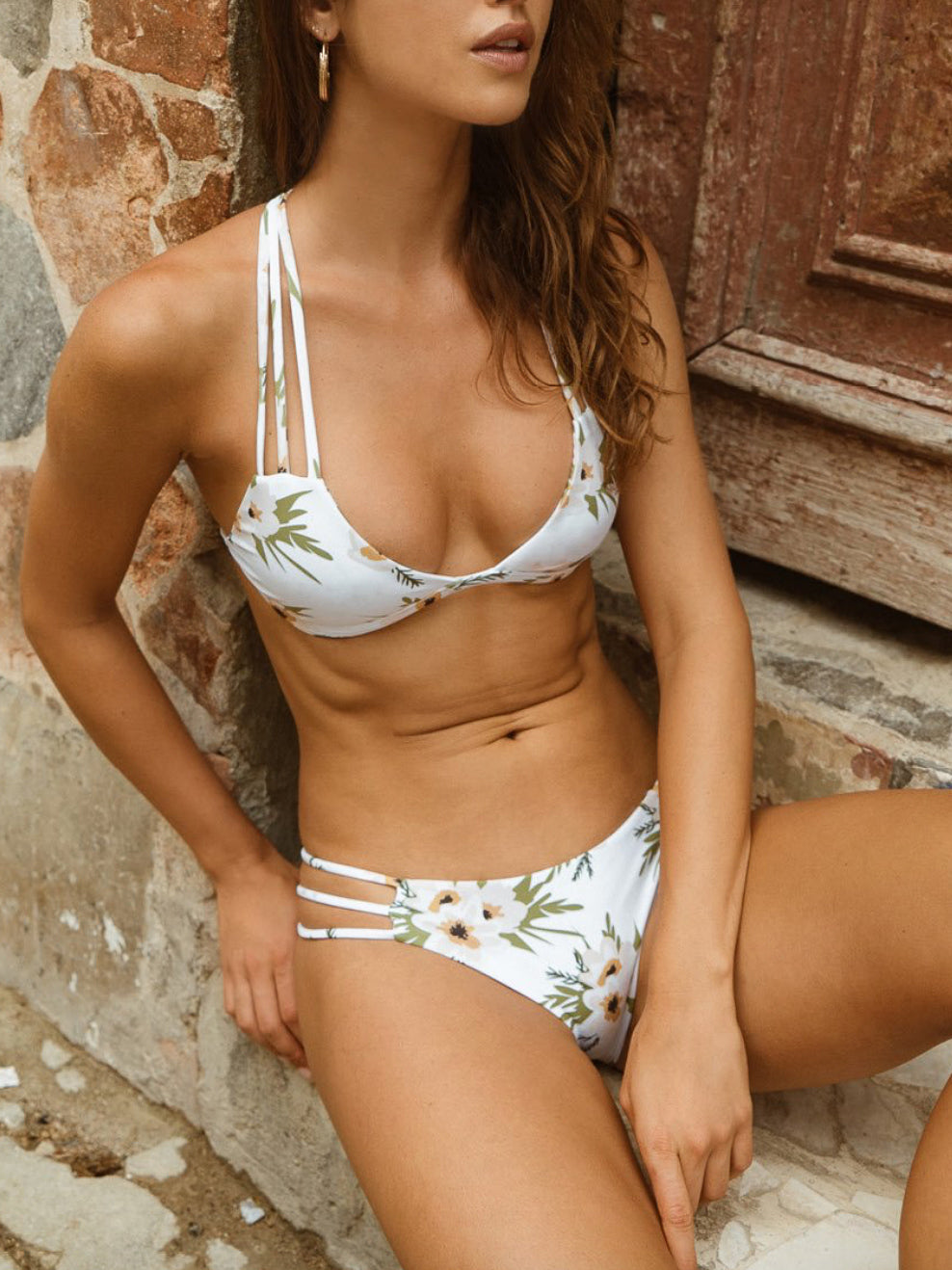 This bikini top is white with a flower print. This top has cross-stitching detail on the back and ties at the neck.