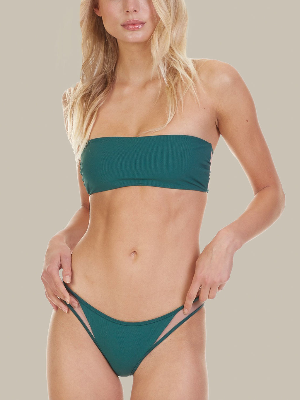 The Tori Praver Manon Bikini Bottoms feature a cheeky bottom and mesh details. They are ribbed and emerald green.