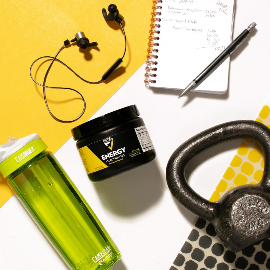 Revel Energy bottle shot on a table with water bottle, kettlebell weight, fitness journal, and headphones