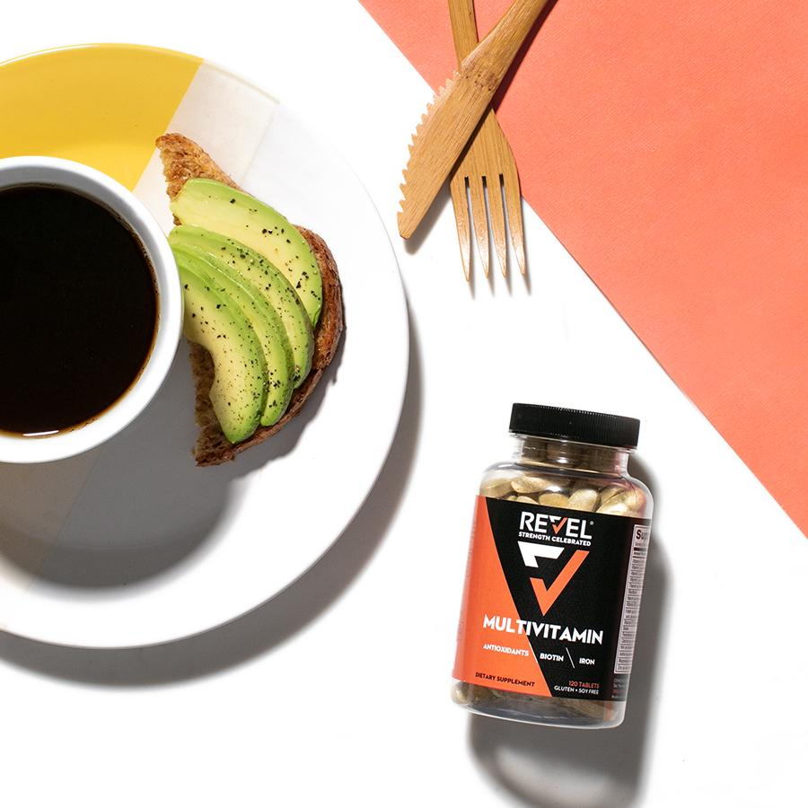 Revel Multivitamin bottle shot on a table with coffee and avocado toast