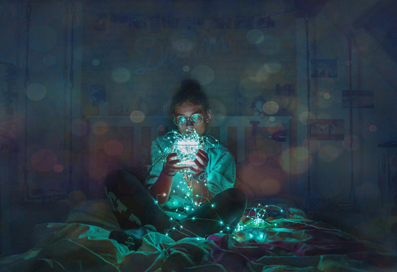 woman holding fairy LED lights on bed in bedroom