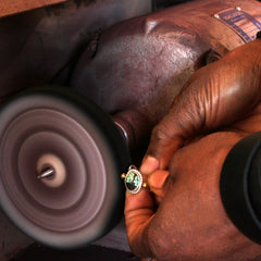 Picture of a persons hands ploishing a piece of jewelry on a buffing wheel