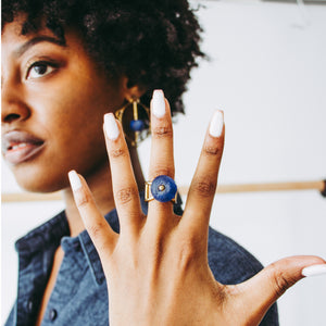 Woman wearing a gold toned Ghanaian Krobo bead ring with =