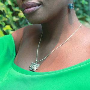 Woman in a green blouse wearing a sterling silver africanmask pendant necklace