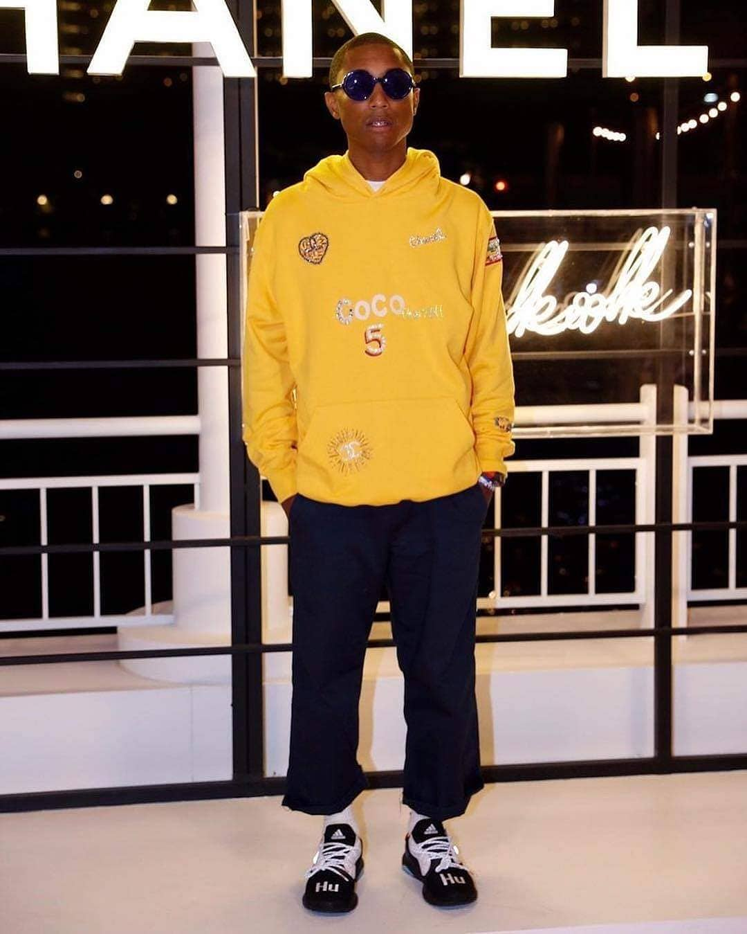 ic: Pharrell Williams during wearing Chanel Pharrell yellow hoodie, sunglasses, striped Adidias trainers and and dark cropped trousers. Source: Instagram