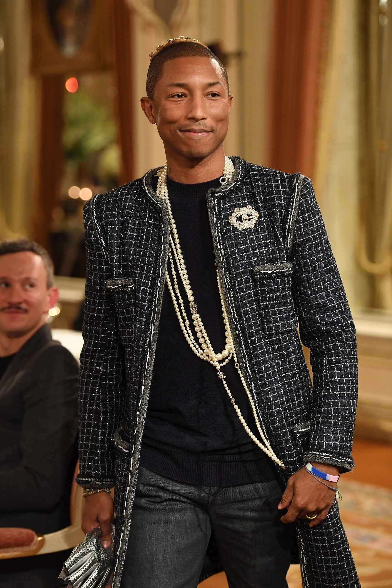 ic: Pharrell Williams at 2016 Chanel Métiers d'Art wearing tweed jacket, pearl necklaces, dark cardigan and grey suit trousers. Source: Vanity Fair