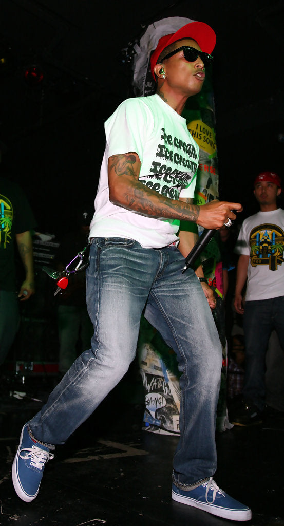 ic: Pharrell wearing slim denim jeans and blue Vans sneakers. Source: Unknown