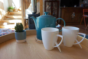 white ergonomic fine bone china cups on tray with teapot
