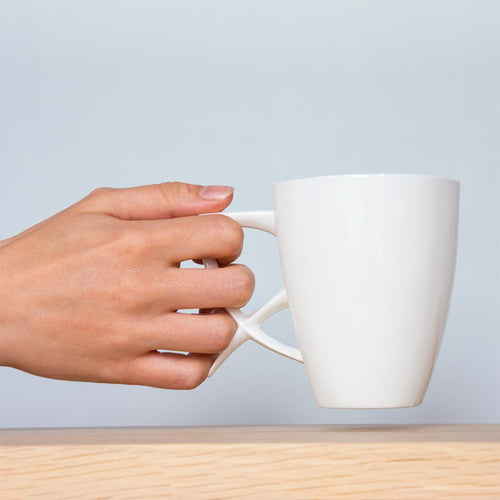 hand holding Three Rowans' white, ergonomic, fine bone china coffee cup