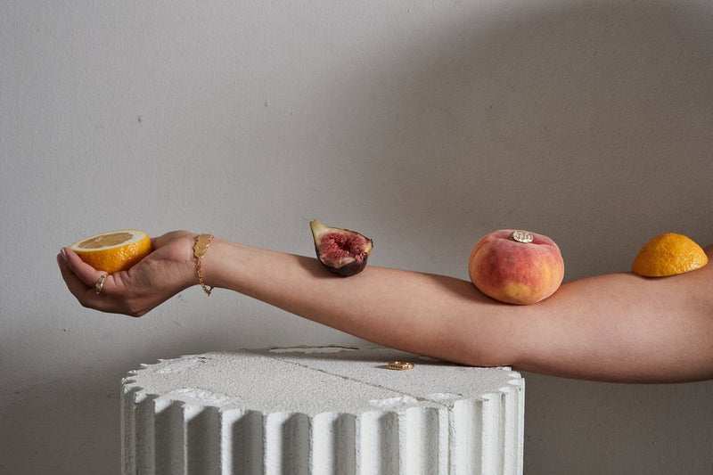 An arm rests on an ancient pillar and holds an orange segment, with a fig, peach and orange balanced on it, wearing decadent jewellery by Gabriella Luchini, including a gold bracelet and gold rings