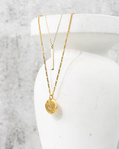 Two gold necklaces hang from a white vase. One necklace is a gold vertical bar, the second necklace features a rough gold coin.
