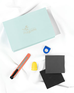 The Magpiette Ring Carving DIY Kit to make sterling silver rings at home, showing the contents which includes a craft knife, wax ring blank, thimble, and two grades of sandpaper