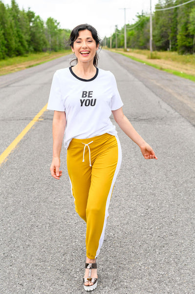 Relaxed white tshirt with 'Be You' front graphic and black neckline trim with a relaxed fit and rounded hemline.