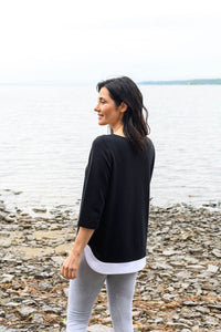 Black, bamboo french terry sweater with a boatneck, three quarter length sleeves and a white, rounded shirttail hem.