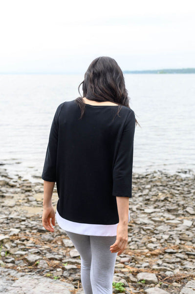 Casual black sweater with a white, rounded shirt tail hem and three-quarter length sleeves.