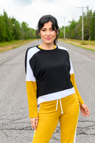 The Haroumi Sweater is a relaxed fit, athletic  sweater with a high-low waist and black, white and mango colour-blocked design.