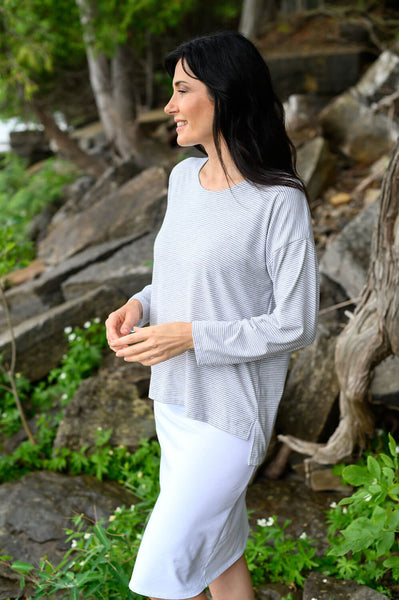 Drop shoulder and high-low hemline details on the white and grey striped sweater made from organic bamboo cotton.