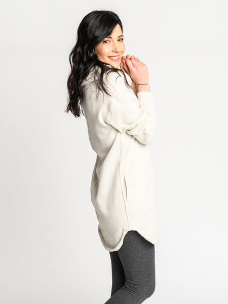 Shaped hem, exposed seam and side pockets on a neutral sweater with a long body and a relaxed fit.