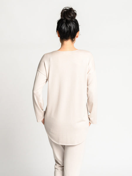 Back of the Crescent sweater in oyster with a high-low hemline.